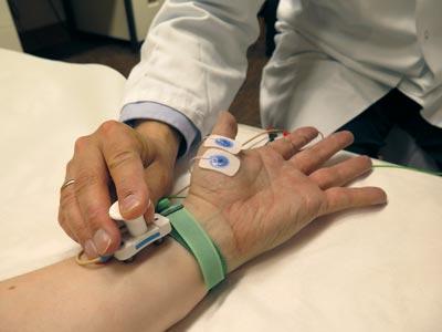 Arzt hält ein Messgerät an den Puls eines Patienten